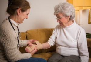 Home healthcare professional wrapping wrist of senior woman